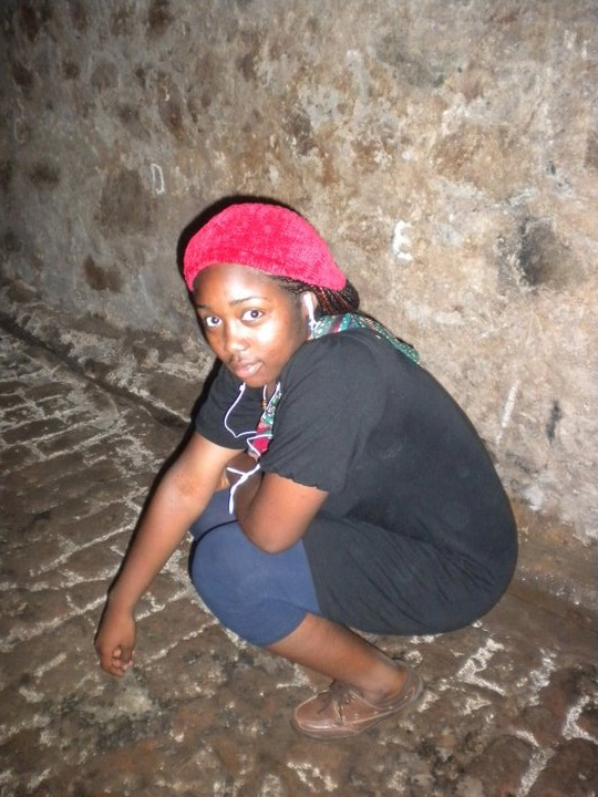 In the male slave dungeon.  Behind me you should see the painted letters representing the fecal levels in the cell.